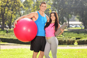 Couple posing in park with fitness equipment