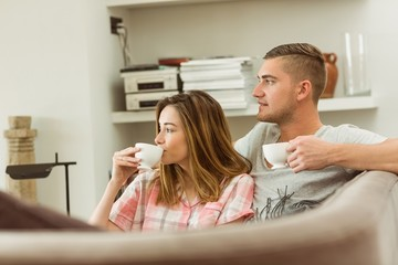 Cute couple relaxing on couch with coffee