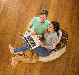 Cute couple using laptop on beanbag