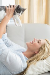 Pretty blonde with pet kitten on sofa
