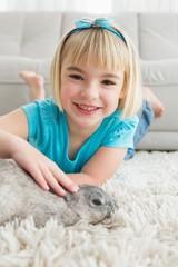 Little girl lying on rug stroking the rabbit