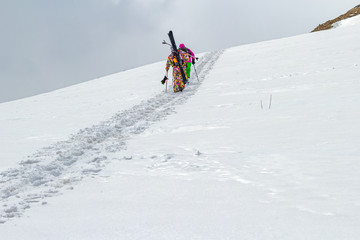 Two skiers rise walk uphill