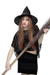 Young girl in witch costume with a broom