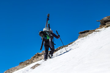 Woman Skier on a background of clear sky rise walk uphill