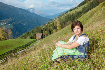 Woman in dirndl sitting on mountain meadow
