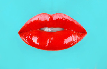 Red lips on turquoise background, closeup
