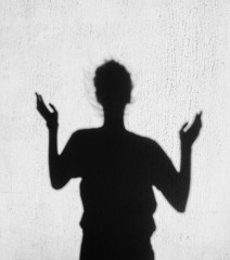 Shadow of girl stretching her hands toward the sky