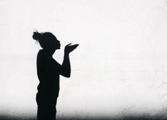Girl sending an air kiss around on the white wall background