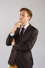 Young businessman thinking with hand on chin