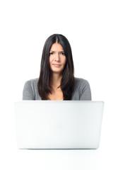 Skeptische junge Frau arbeitet mit einem Laptop