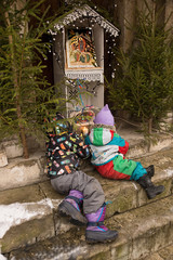 Two children sit at temple steps at Christmas icon
