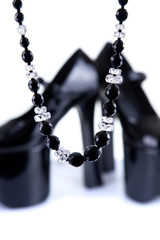 Pair of black platform shoes with necklace
