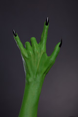 Green monster hand with black nails showing heavy metal gesture
