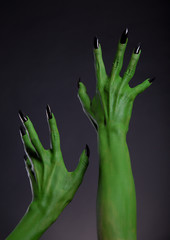Green monster hands with black nails stretching up, real body-ar