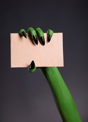 Green skin hand with sharp nails holding empty piece of cardboar