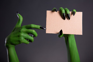 Green monster hand with black nails pointing on blank piece of c