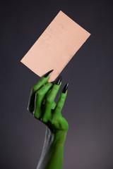 Green monster hand holding blank piece of cardboard