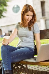 Woman with disposable cup and laptop sitting on bench