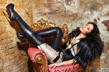 Beautiful sexy woman in black fur Treads sitting on the chair