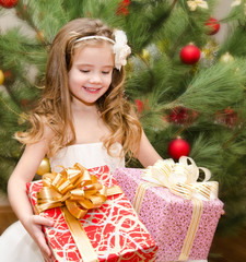 Happy adorable little girl with gift boxes