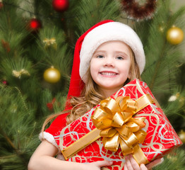 Cute smiling little girl in santa hat with gift box