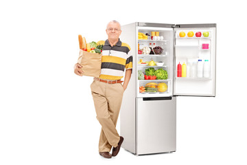 Man holding bag with groceries by an open fridge