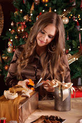 Beautiful young woman decorating a christmas present