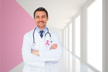 Composite image of handsome young doctor with arms crossed