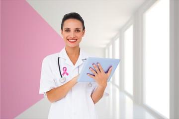 Composite image of pretty nurse using tablet pc