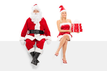 Man and woman in santa costume sitting on a panel