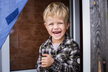 Cute little blond boy laughing. Happiness