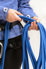 Rock climber wearing safety harness rolling climbing rope