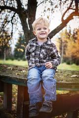 Beautiful blond kid sitting outdoor on table. Autumn