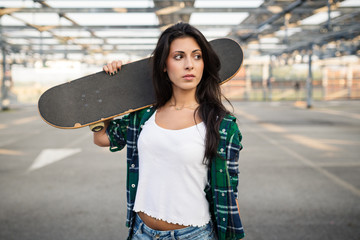 Teenager with skateboard portrait outdoors in a parking area.