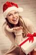 Happy smiling Santa girl with gift box enjoying snowflakes