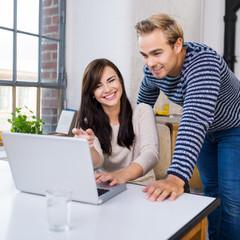 modernes paar schaut gemeinsam auf laptop