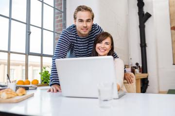 glückliches paar mit laptop in ihrer wohnung