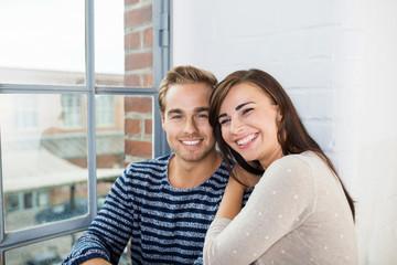lachendes junges paar sitzt zuhause am fenster