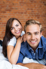 glückliches attraktives paar liegt auf dem bett