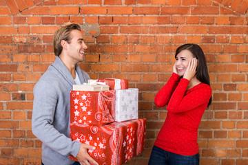 lachendes junges paar mit vielen geschenken