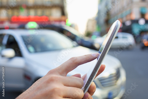 Woman ordering a taxi from her mobile phone - 71645869