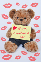 Teddy bear holding a yellow sign that says Happy Valentine's Day