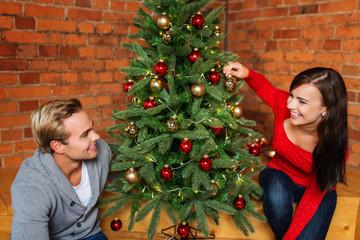 glückliches junges paar schmückt den weihnachtsbaum