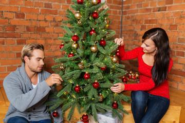 junges paar schmückt den weihnachtsbaum