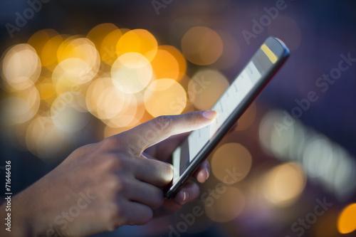 Woman using her mobile phone , city skyline night light