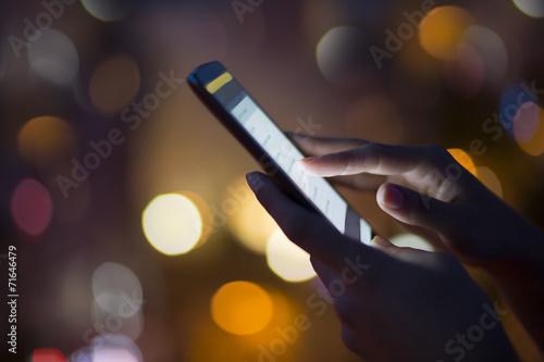 Leinwanddruck Bild Woman using her mobile phone , night light background