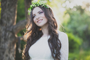 Young beautiful smiling woman in the sunset forest