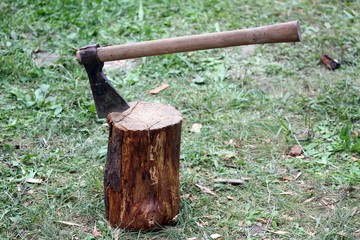 great axe with blade of steel over wood log
