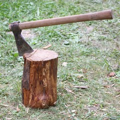 big lumberjack's axe stuck in wooden log
