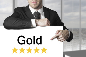 businessman pointing on sign gold